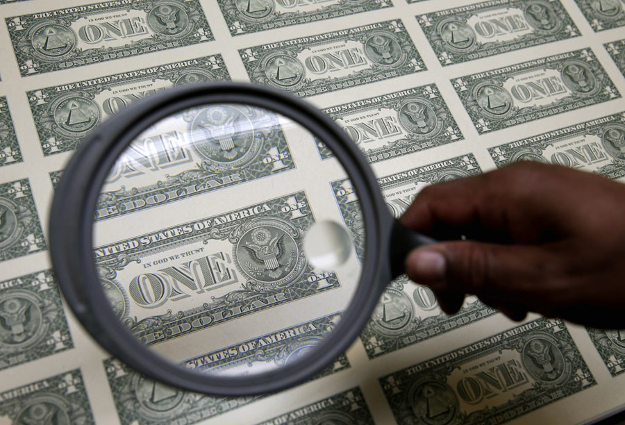 United States one dollar bills are inspected under a magnifying glass during production at the Bureau of Engraving and Printing in Washington