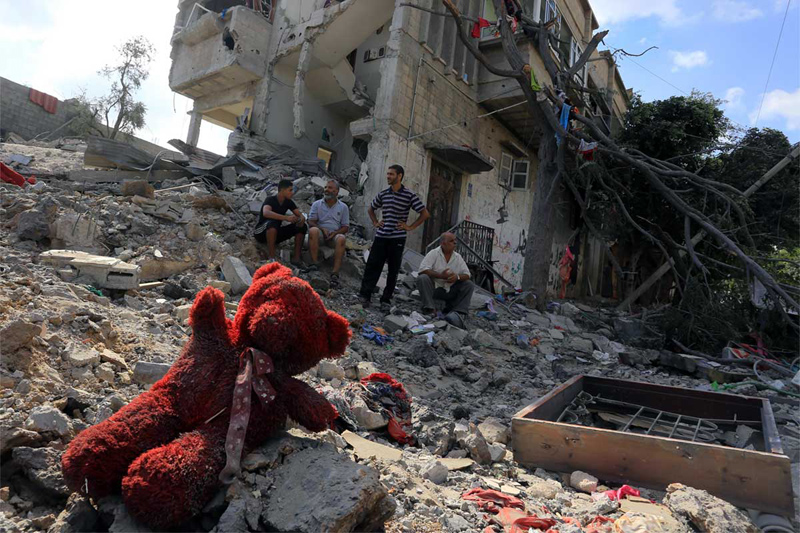 Operation Protective Edge Man in rubbles of bombed out home child's teddy bear left