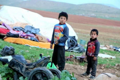 Palenstine: 2 young boys standing in front of a makeshift tent after homes destroyed 2021-02