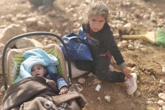 Palenstine: Little girl toddler next to a baby in their bassinet, outside sitting on dirt, in the rubble where they are now forced to survive 02