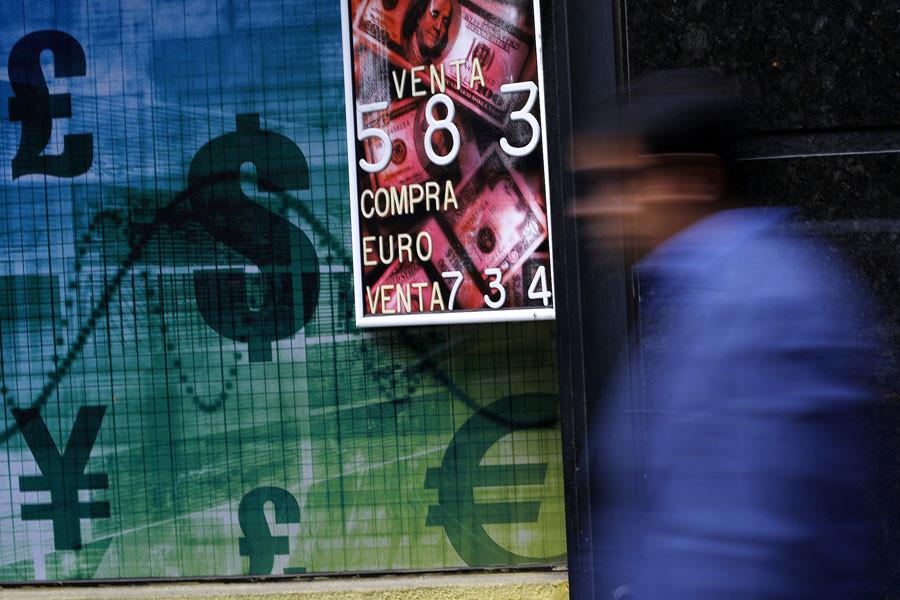 A pedestrian walks past a money exchange bureau in downtown Santiago
