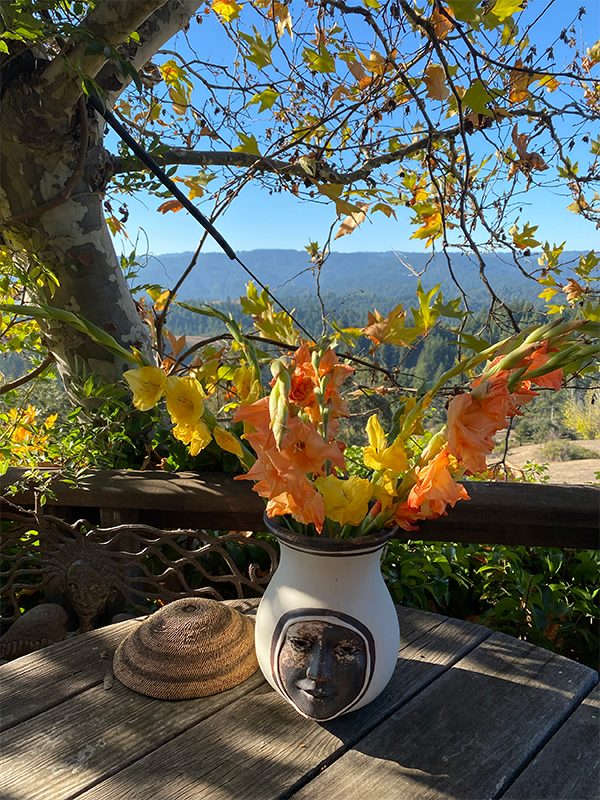 outdoor vase with womans face fresh flowers on wooden table old tree view of land hills background