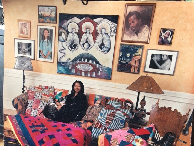 Alice with her dog, Mbele, SF,  the 90s on couch covered with quilts, art on wall