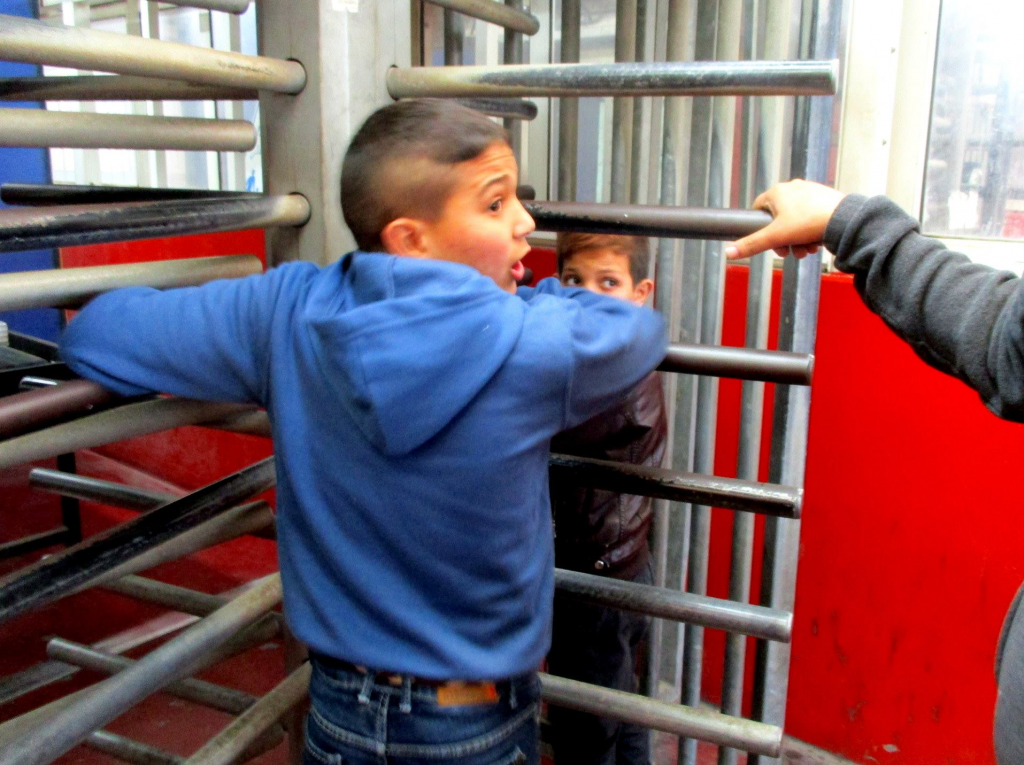 Young Palestinian Boy at turnstyle gates Israeli Settlements