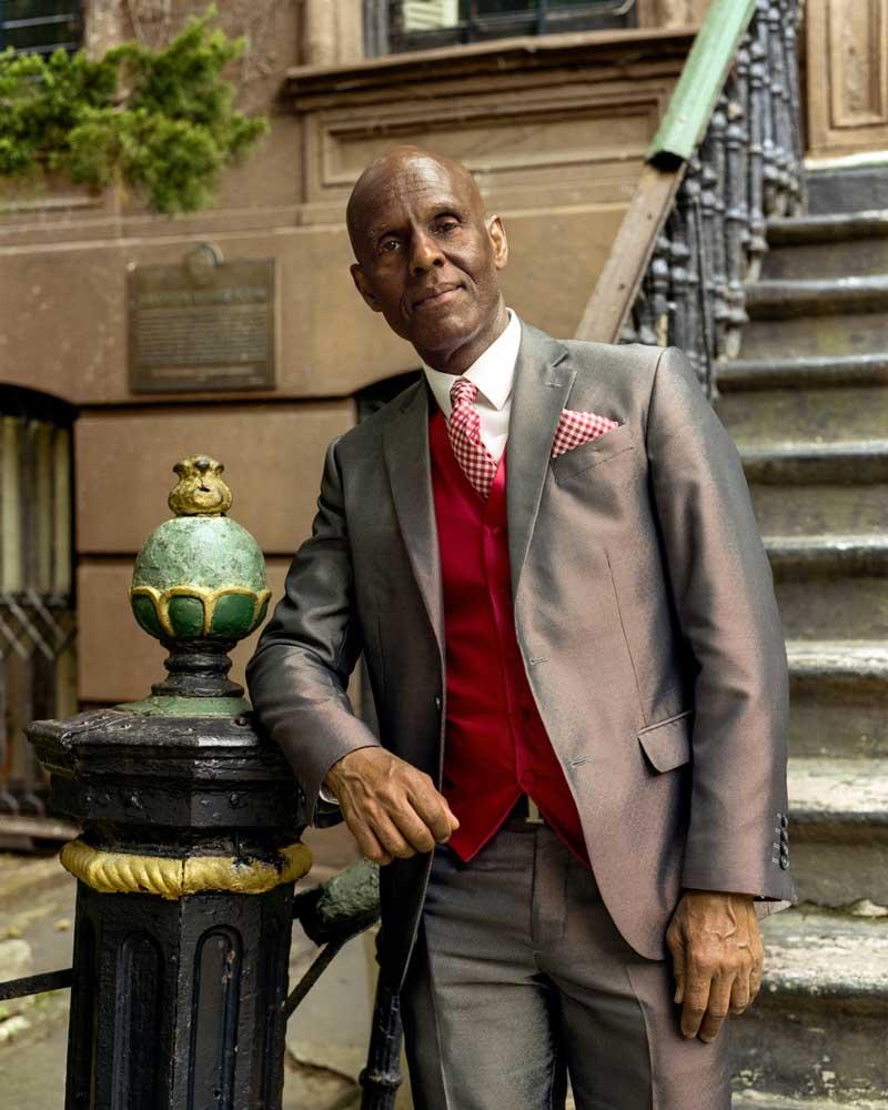 Dapper Dan standing in front of building wearing shiny suit red vest tie