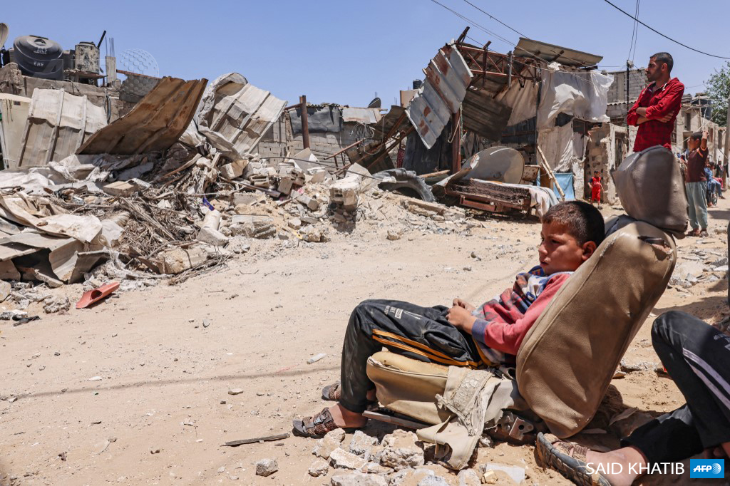 Gaza child sitting in car seat in the destruction of his town