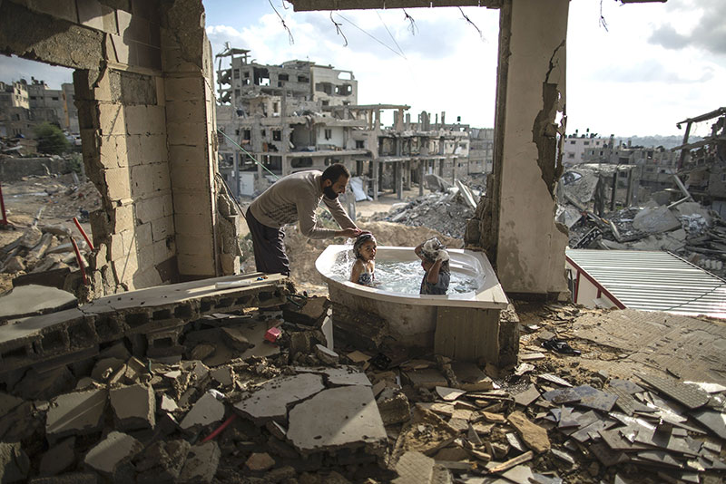 Bathtub only thing left after bombing. Father bathing his 2 children.