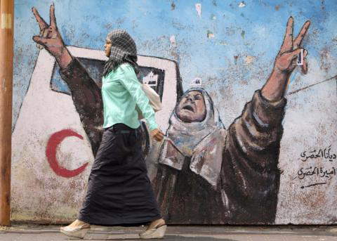 Gaza Woman walking past Mural